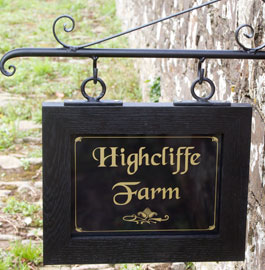 Wooden Framed Sign hanging from wrought iron bracket