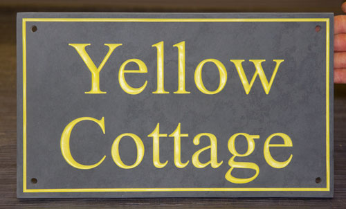 Slate sign with yellow text and line border