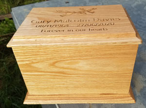 A simple tall oak ashes casket.