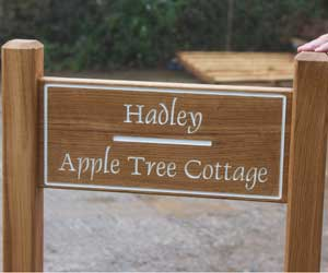 Wooden entrance sign morticed into two oak posts. Font - Dauphin