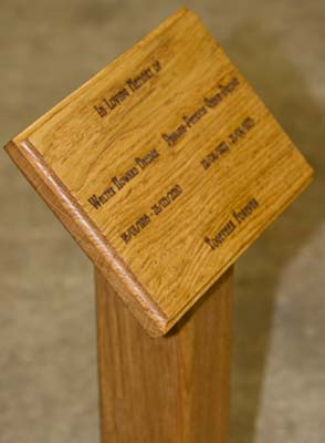 Wooden memorial plaque fixed to post with wooden dowels
